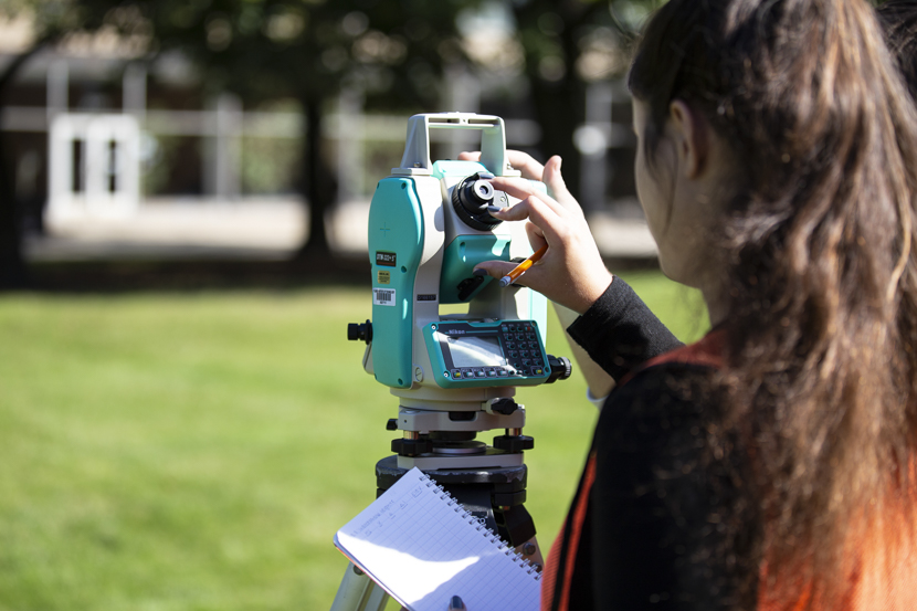 A student utilizes surveying equipment during a Civil Engineering class