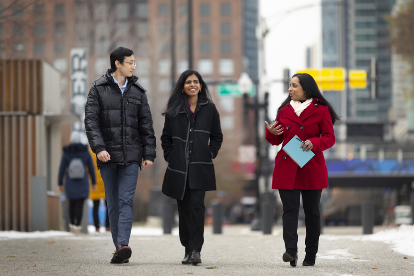 Two students and an alumna walk outside of Navy Pier where the three of them work