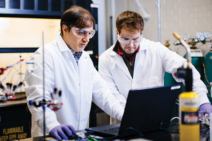 A graduate faculty member working with a student inside an engineering lab