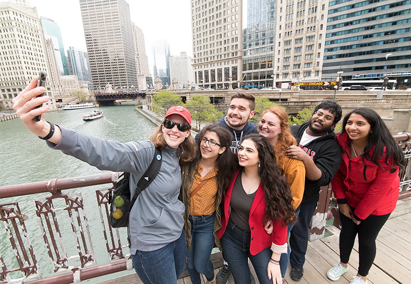 Multiple undergraduate students taking a selfie in downtown Chicago