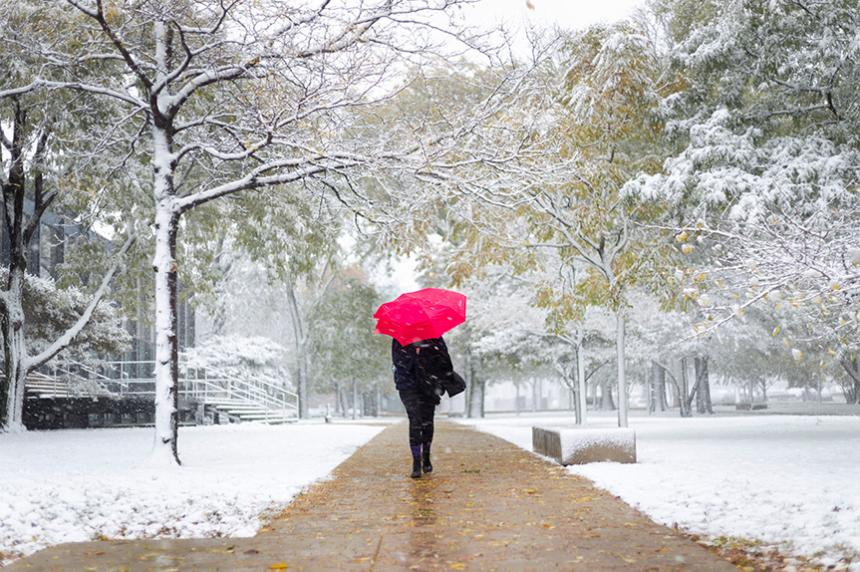 A student walking in the snow on Mies Campus carrying a red umbrella