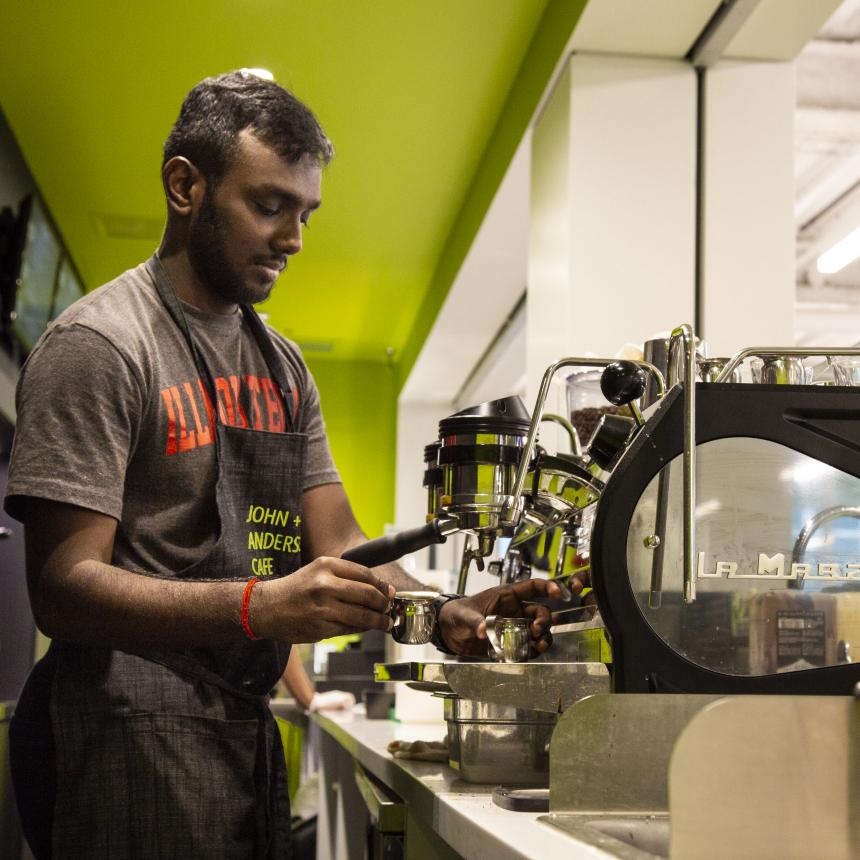 A student worker makes a latte in the cafe in Kaplan Institute