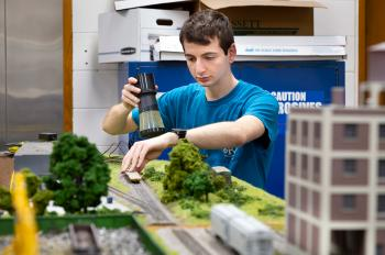 Daniel Rappoport adds grass to this section of model railroad in Alumni Hall.