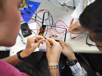 Students work on a circuitboard together