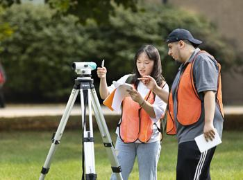 Civil Engineering - photo of students outdoors with a transit on a tripod
