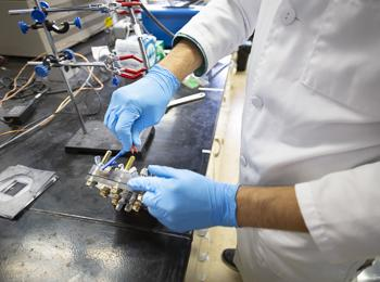 A researcher puts together a fuel cell in Mohammad Asadi's lab
