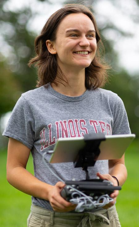Photo of student Sydney Kaplan operating a drone as part of her research at the Morton Arboretum.