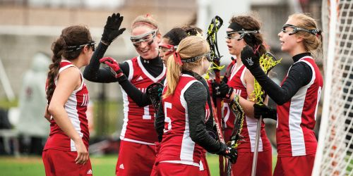 Women's lacrosse team giving each other a high five