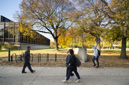 Outdoor photo of students walking on campus in autumn, showing Galvin library