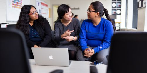 Photo of professor and students sitting together with a computer