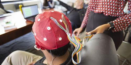 A student demonstrates how an EEG is performed in a Psychology class