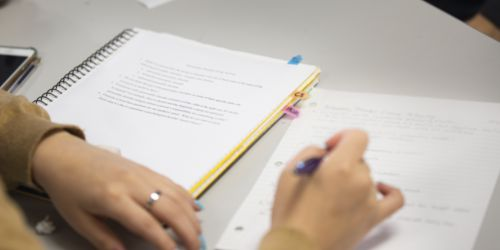 A student takes notes in a Lewis College class