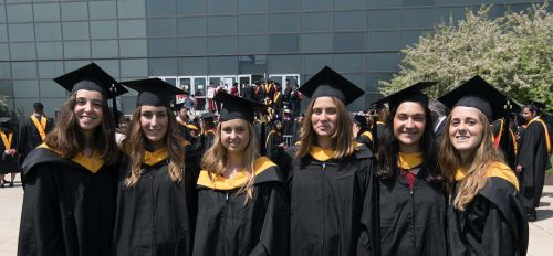 Multiple female graduate students standing outside together at the graduation ceremony