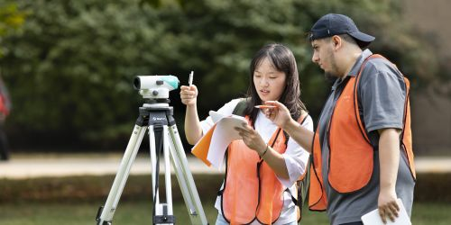 Two students survey a plot of land during a civil engineering class