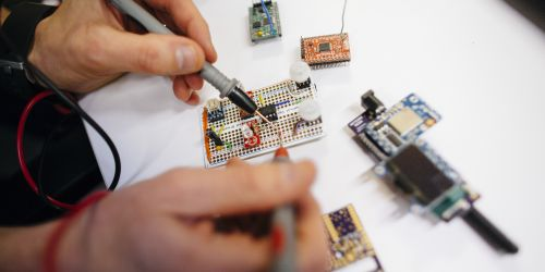 A researcher works to built a circuitboard