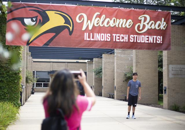 A student has his picture taken under a banner during move-in day