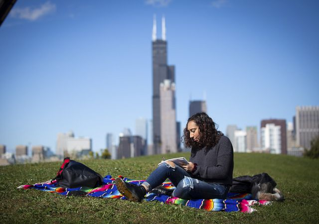 A student studies with the chicago skyline in the background