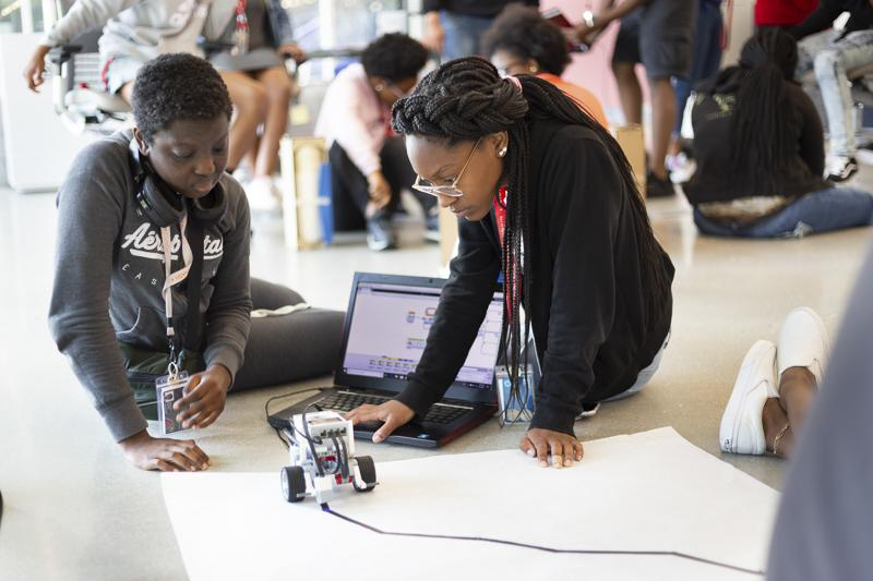 Students work to program a robot during a summer course