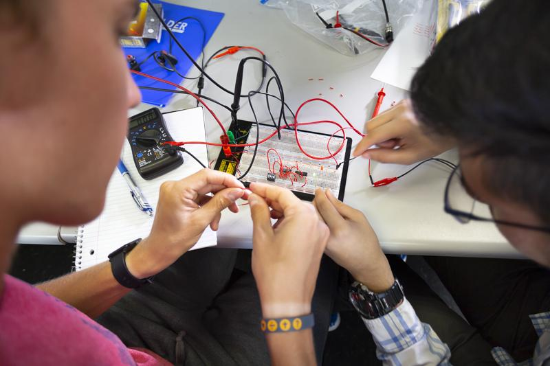 Students work on a circuitboard in an electrical engineering class.