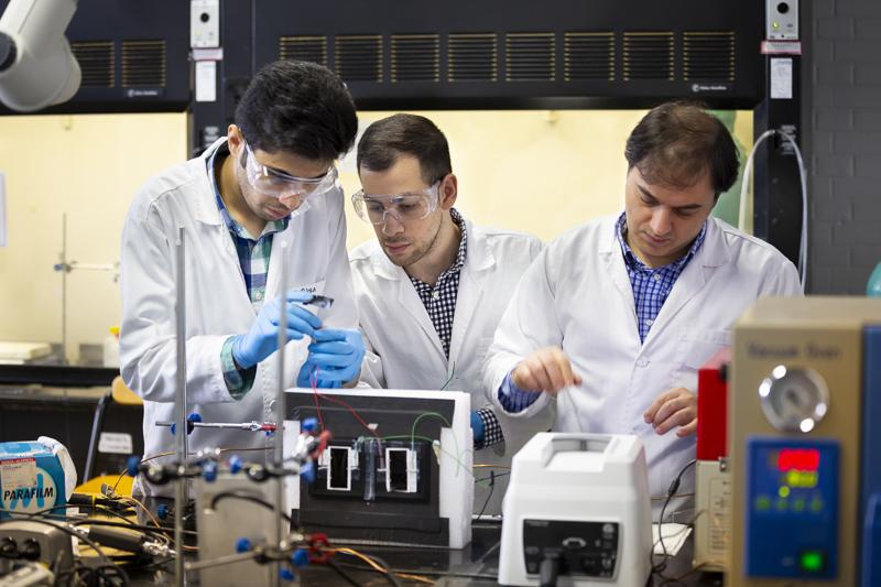 Graduate students work in an electrical engineering lab with their professor.