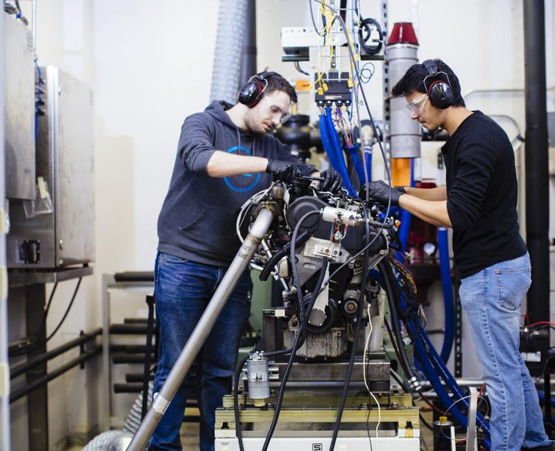 Two students work on an engine at Armour College of Engineering