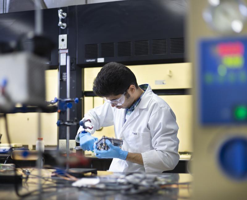 A student researcher works on a fuel cell in a chemical engineering lab
