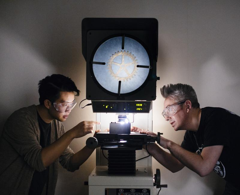 Two students examine a gear in a materials lab