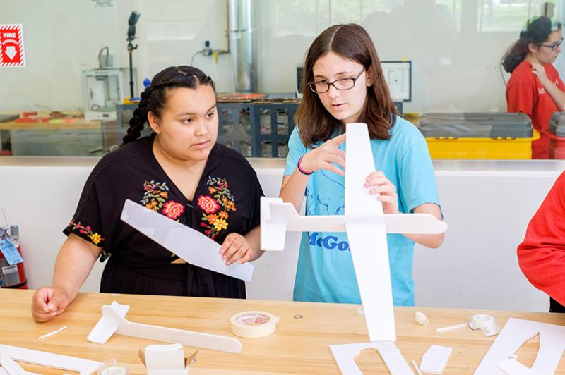 Two female students working on an airplane project during a summer class