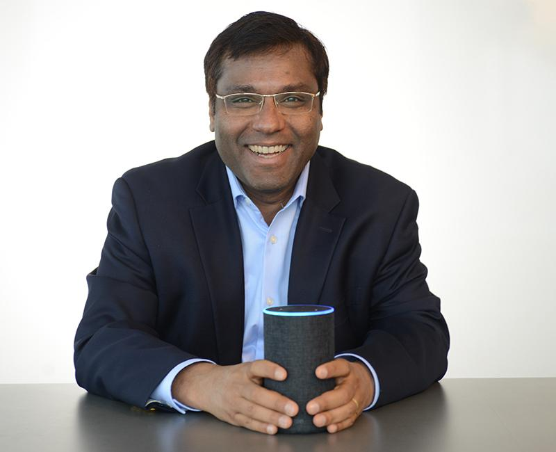 A photo of Rohit Prasad holding Alexa