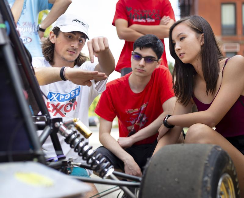 A member of the IIT motorsports club explains mechanics to two students
