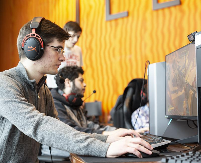 A student plays a video game in the Esports lab