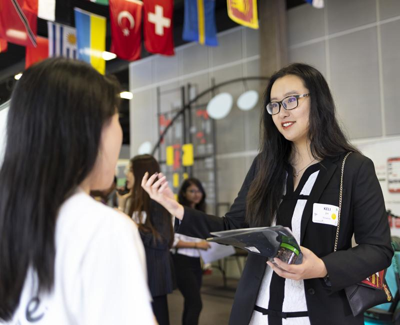 A student speaks with a potential employer at a career fair.