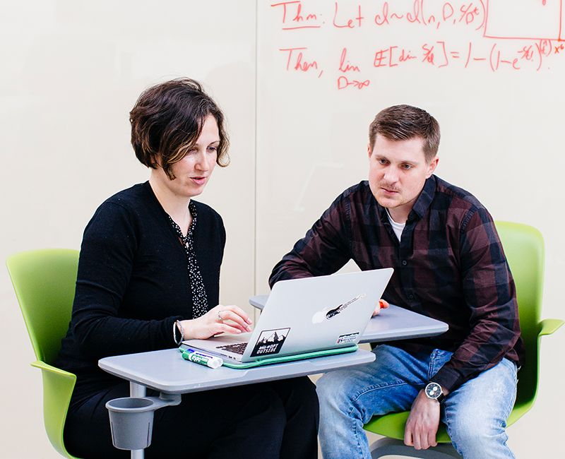 A faculty member talking to a student in an open study space