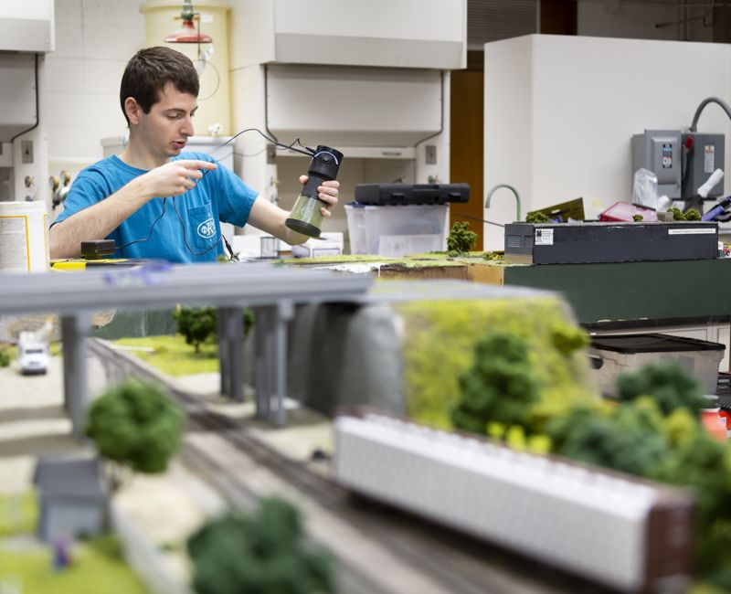 A student in the model railroad association lays grass on a model