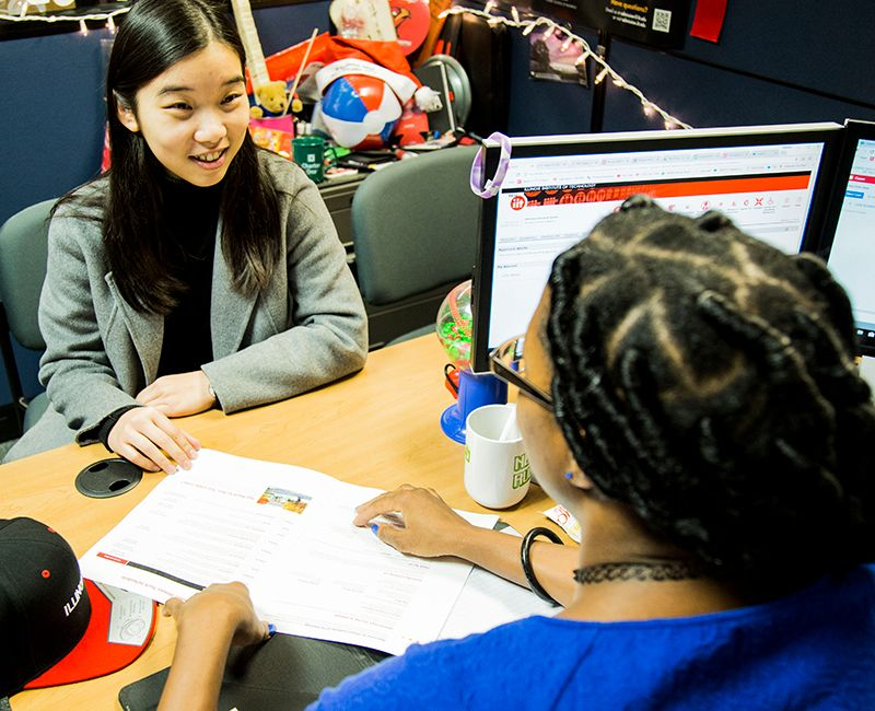 A staff member talking to a student giving advising